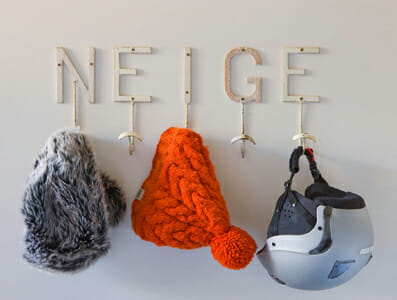 Warm hats and ski helmet hanging on 'Neige' wall hanger.